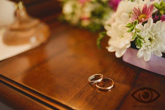 obruchalnye-kolca-na-derevjannom-stole-cvety
